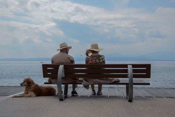Elderly couple and dog at seaside.